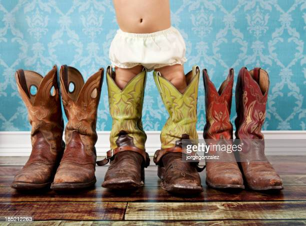 baby wearing her daddy cowboy boots