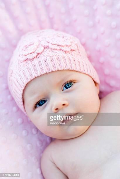 Baby wearing pink beanie lying on pink blanket