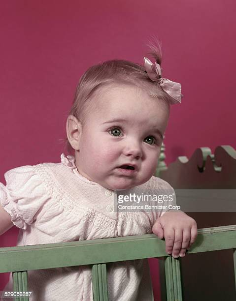 Baby wearing pink bow and pink shirt standing in crib looking sad and confused