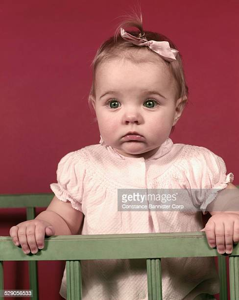 Baby wearing pink bow and pink shirt standing in crib looking sad