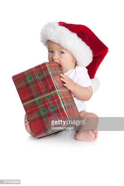 Baby Wearing Santa Christmas Hat Chewing on Wrapped Gift
