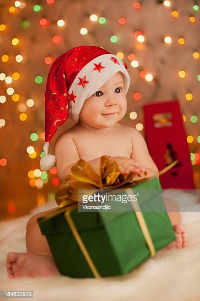 Baby wearing Santa hat holding green and gold present