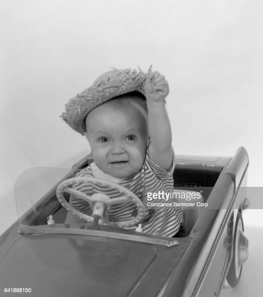 baby wearing straw hat in toy car - number of people stock pictures, royalty-free photos & images