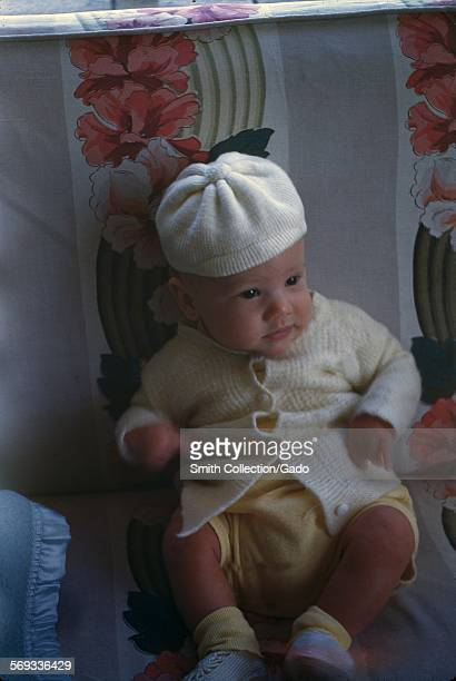 Baby wearing yellow knitted clothing on a floral print chair 1949