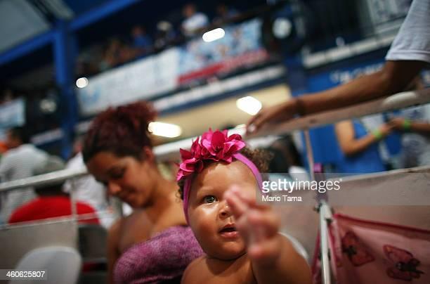 A baby wears a ribbon at a traditional samba and feijoada party held at the Portela Samba School in the Madureira neighborhood during preCarnival...