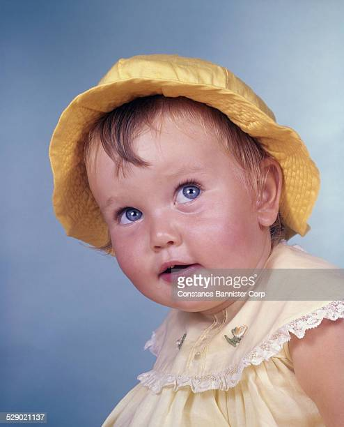 Baby with big blue eyes wearing a yellow dress and bright yellow hat
