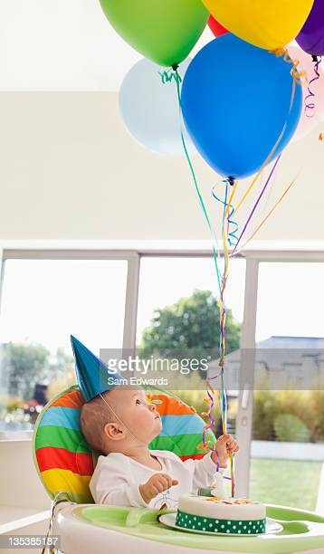 bebê com bolo de aniversário a segurar balões - first birthday imagens e fotografias de stock