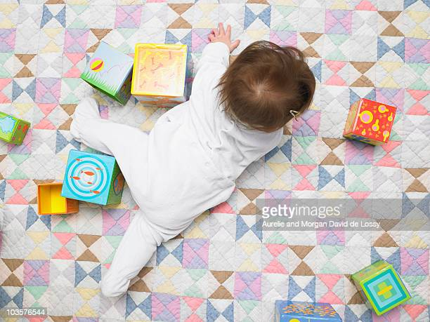 Baby with cubes on quilt