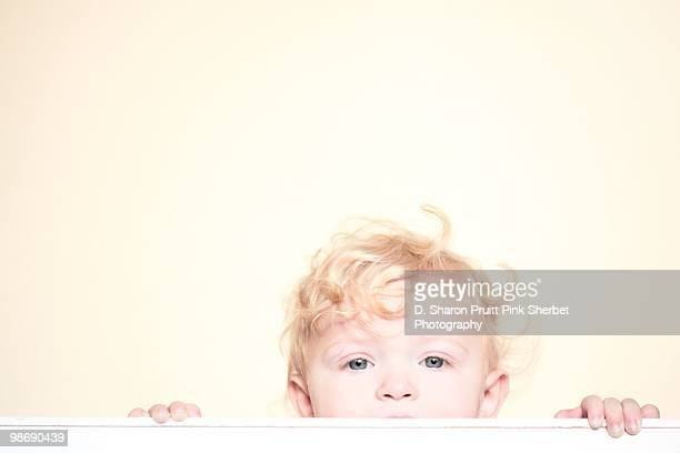 Baby With Curly Hair Peeking Over Crib