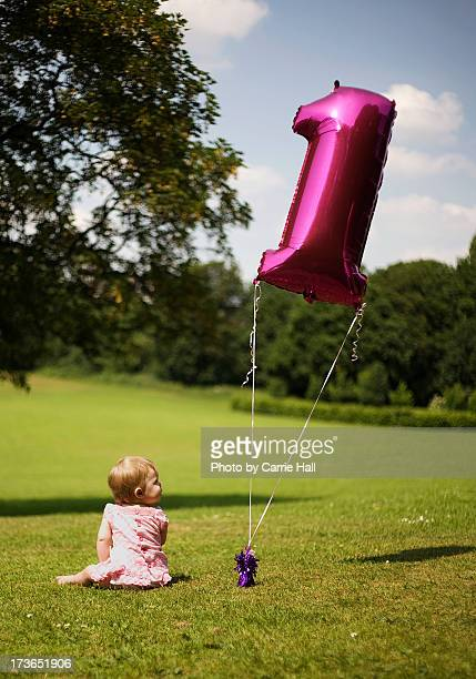 Baby with first birthday balloon