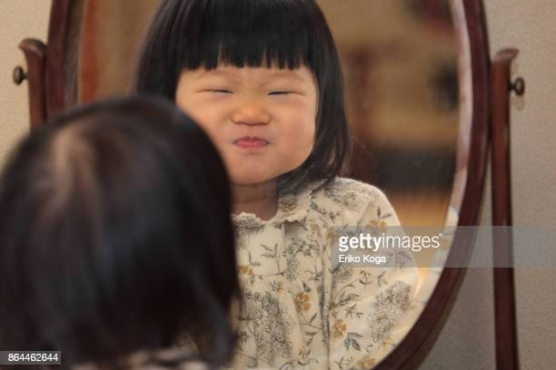 Baby with funny face in mirror