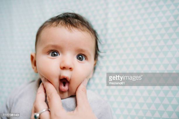Baby with funny face, mother's Hand pressing her cheek