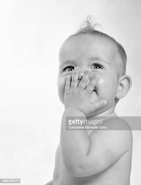 baby with hand on mouth - constance bannister stock photos and pictures