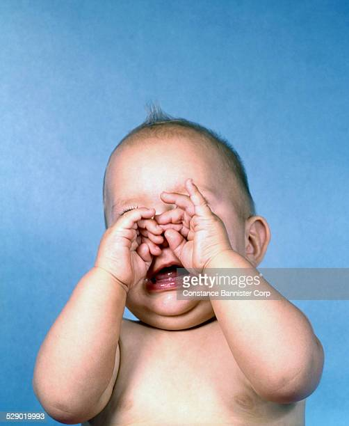 Baby with hands over eyes and mouth open crying