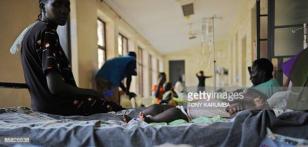 A baby with malaria lays in bed as her mother sits nearby in a malaria ward on April 2 2009 in the main hospital in Juba where the population is...