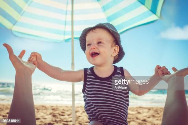 baby with mother on the beach - parasol stock pictures, royalty-free photos & images