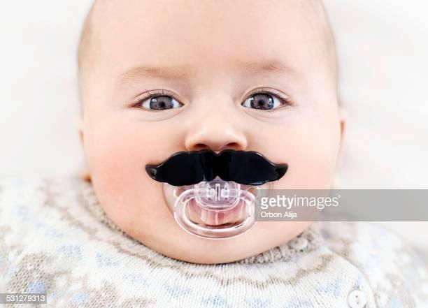 Bebé con bigote chupete