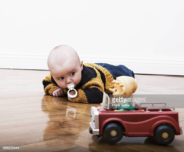 Baby with Pacifier and Toy Car on Wood Floor