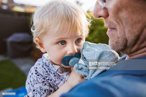 Baby with pacifier in father's arm