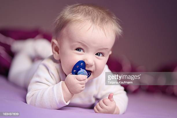 Baby with pacifier shows a 'thumbs up'