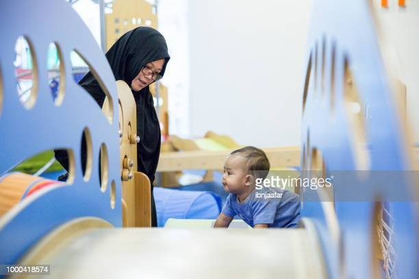 baby with parent at baby gym - ibnjaafar stock photos and pictures