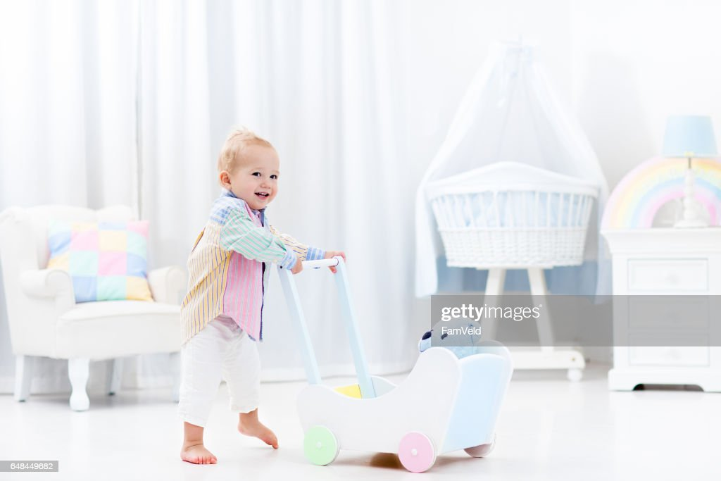 Baby with push walker in white bedroom : Stock Photo