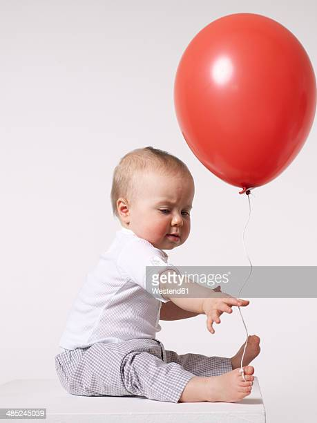 Baby with red balloon