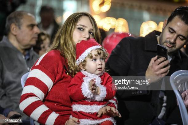 A baby with Santa Claus costume is seen as people gather around an illuminated christmas tree at yard of Christian Youth Association as part of...
