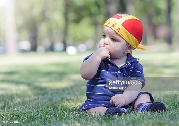 Baby with spanish handkerchief sitting on grass