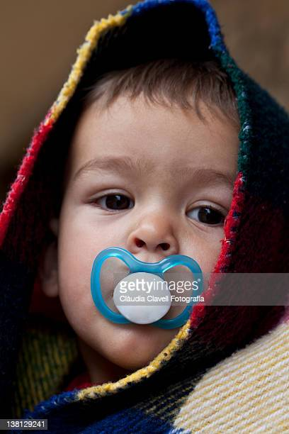 Baby wrapped in blanket with pacifier