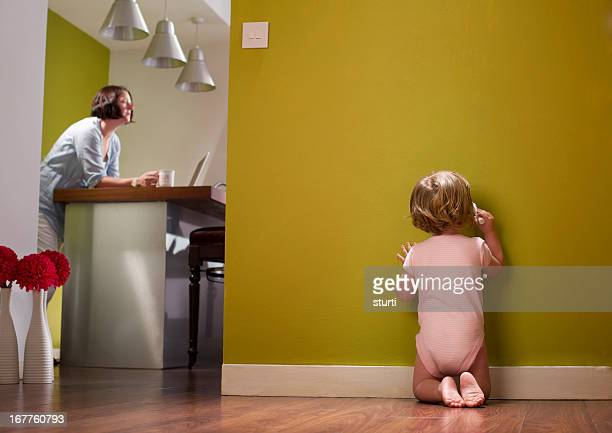 baby writes on wall whilst mother is oblivious