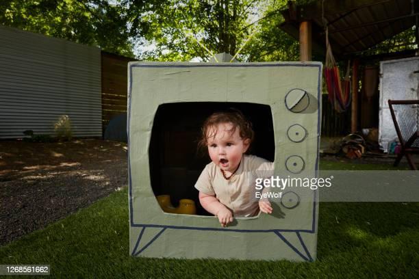 a babyclimbing out of a cardboard tv - insight tv stock-fotos und bilder
