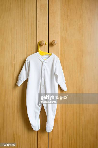babygro hanging on wardrobe - infant bodysuit stock pictures, royalty-free photos & images