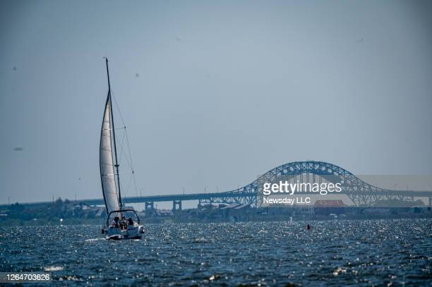 Sailboat slowly moves towards the open waters in the Great South Bay off of Sampawams Point with the Robert Moses Bridge in the background in...