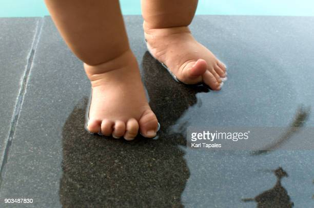 A baby's feet is wet in the pool