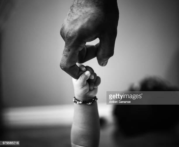baby's hand holding father's finger - braccialetto foto e immagini stock