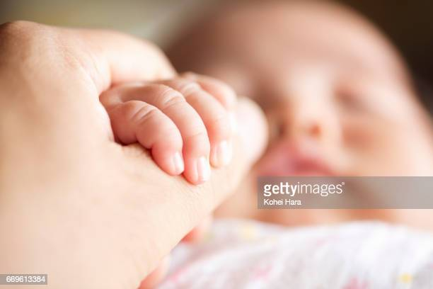 Baby's hand holding her father's hand