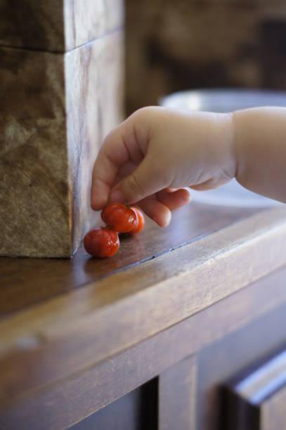 A baby's hand picking up pitanga