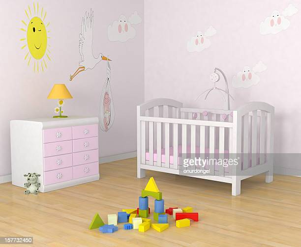 Baby's room with decor, crib, toys and a dresser with lamp