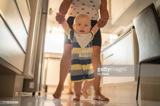 o bebé de ajuda da babá aprende andar em casa - amas - fotografias e filmes do acervo