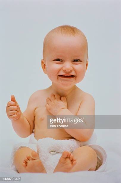 Baby(6-12 months)wearing towelling nappy, smiling, white background