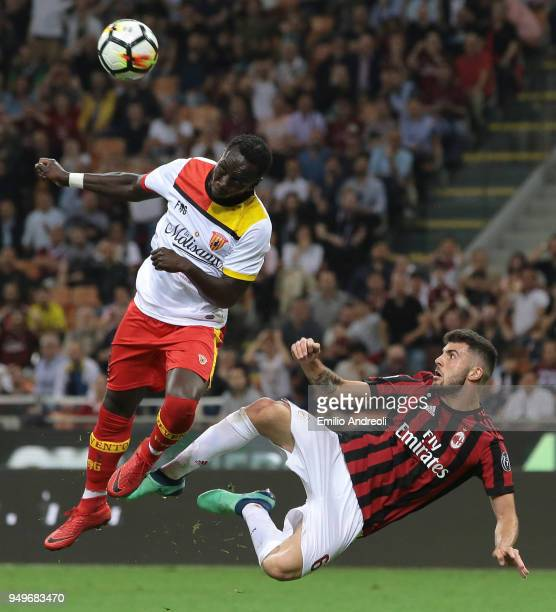 Bacary Sagna of Benevento Calcio jumps for the ball against Patrick Cutrone of AC Milan during the serie A match between AC Milan and Benevento...
