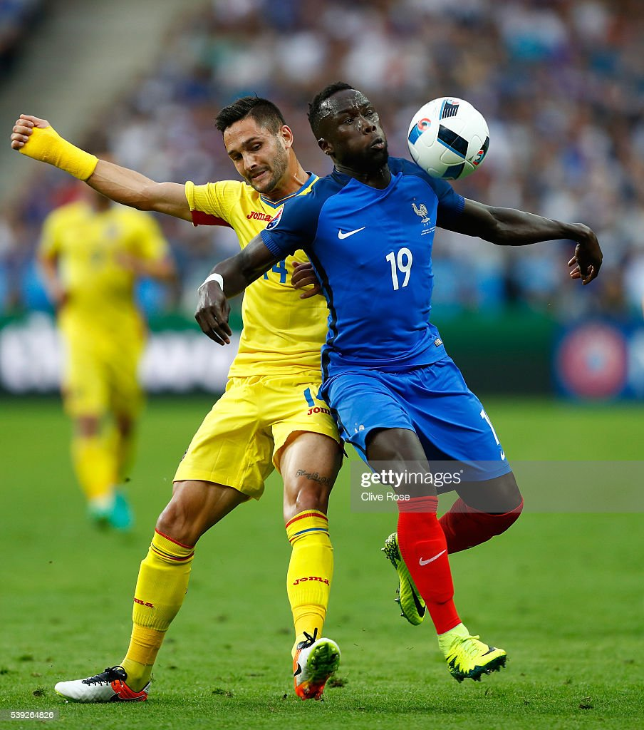 Bacary Sagna of France and Florin Andone of Romania compete for the ball during the UEFA Euro 2016 Group A match between France and Romania at Stade de France on June 10, 2016 in Paris, France.