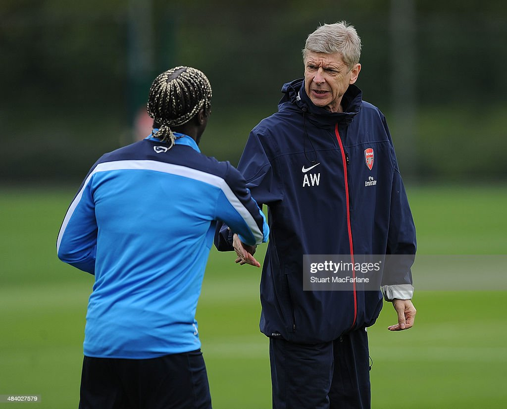 ST. ALBANS, ENGLAND - Bacary Sagna shakes hands with Arsenal manager Arsene Wenger before a training session at London Colney on April 11, 2014 in St Albans, England.