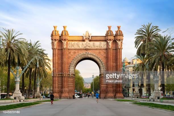 bacelona arc de triomf during sunrise in the city of barcelona in catalonia, spain. the arch is built in reddish brickwork in the neo-mudejar style - barcelona fotografías e imágenes de stock