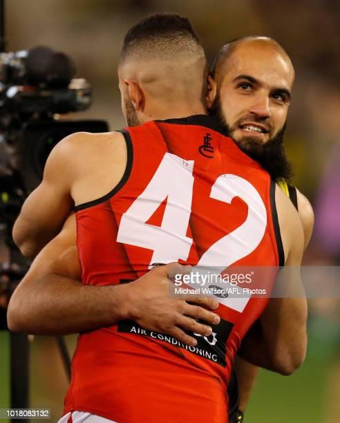 Bachar Houli of the Tigers and Adam Saad of the Bombers embrace before the coin toss during the 2018 AFL round 22 match between the Richmond Tigers...