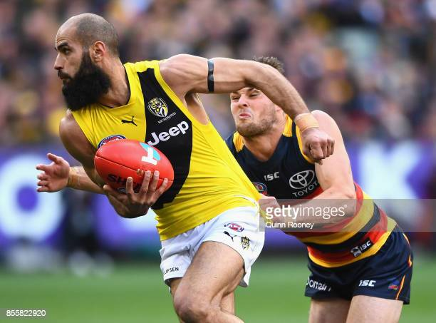 Bachar Houli of the Tigers handballs whilst being tackled during the 2017 AFL Grand Final match between the Adelaide Crows and the Richmond Tigers at...