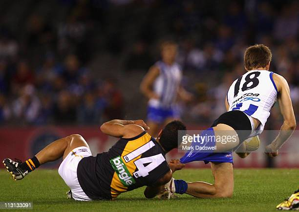 Bachar Houli of the Tigers rips the shorts off Shaun Atley of the Kangaroos during the round five AFL match between the North Melbourne Kangaroos and...