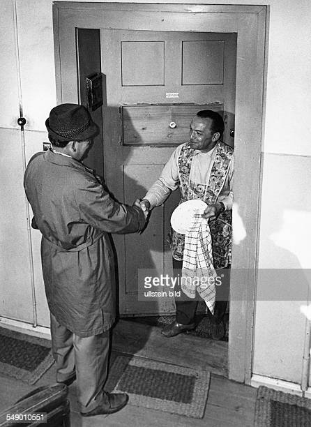 Bachelor openiíng the door to a friend. Late fifties