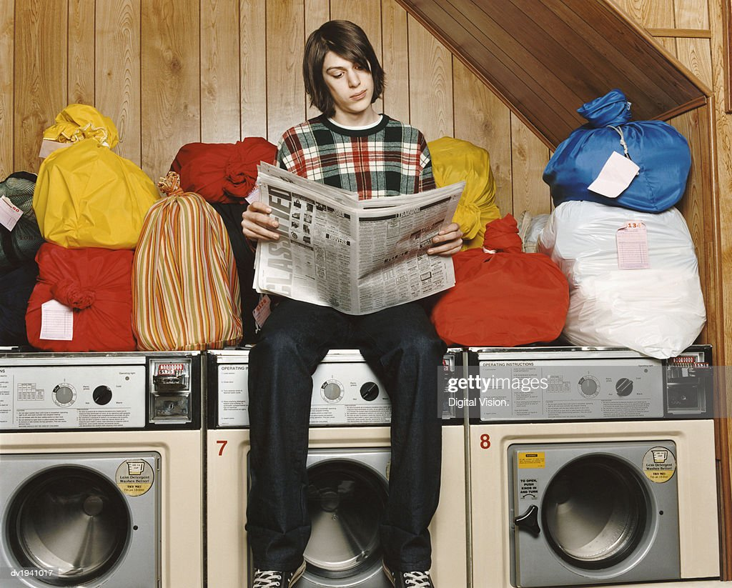 Bachelor Sitting On Top of a Washing Machine and Reading a Newspaper in a Launderette : Stock Photo